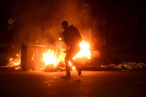 a-woman-passes-burning-garbage-during-a-demonstration-in-oakland-california-us-following-the-ele